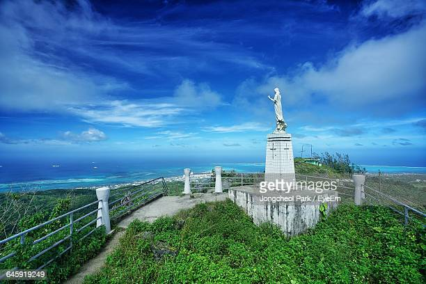 statue of jesus christ at mount tapochau against cloudy blue sky - saipan stock pictures, royalty-free photos & images
