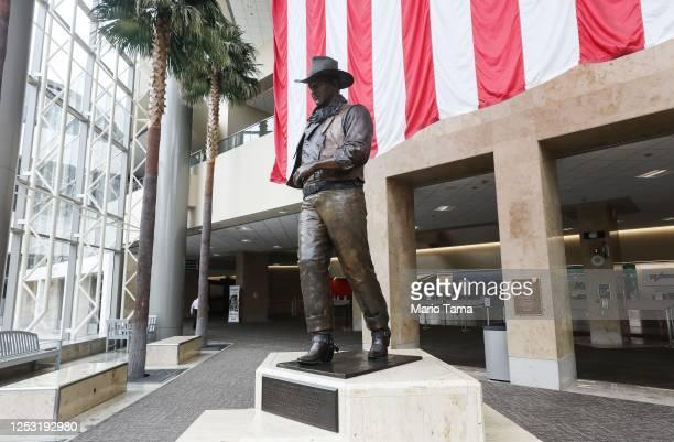 A statue of John Wayne is on display beneath an American flag in John Wayne Airport located in Orange County on June 28 2020 in Santa Ana California...