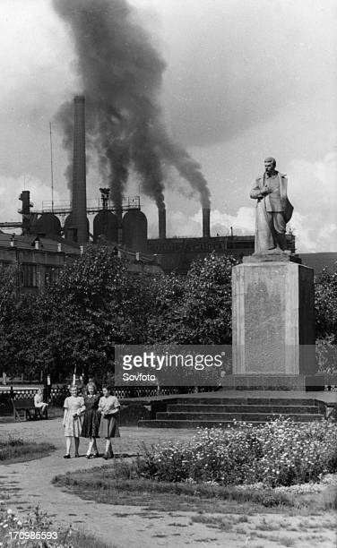 A statue of joseph stalin in the garden of victory square in the industrial city of stalinsk the iron and steel plant is in the background spewing...