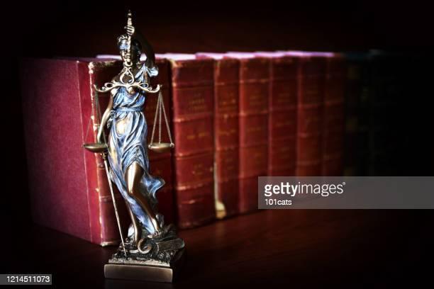 estatua de la justicia frente a los libros de leyes - themis - abogado fotografías e imágenes de stock