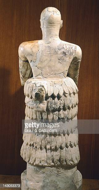 Statue of King IturShamagan praying wearing a wool sheep cloak rear view Artefact from Mari archeological site Syria Assyrian civilisation 3rd...