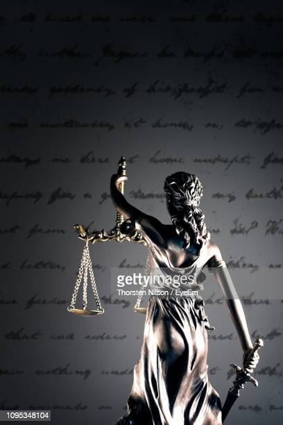 Statue Of Lady Justice Against Document