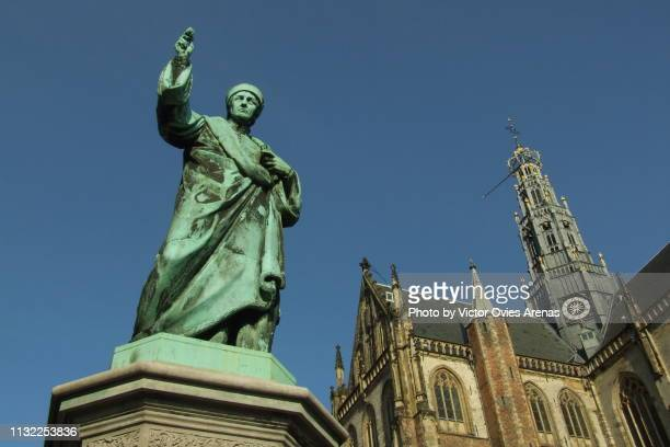 statue of laurens coster and st. bavo church (grote kerk) in haarlem, netherlands - haarlem stock photos and pictures
