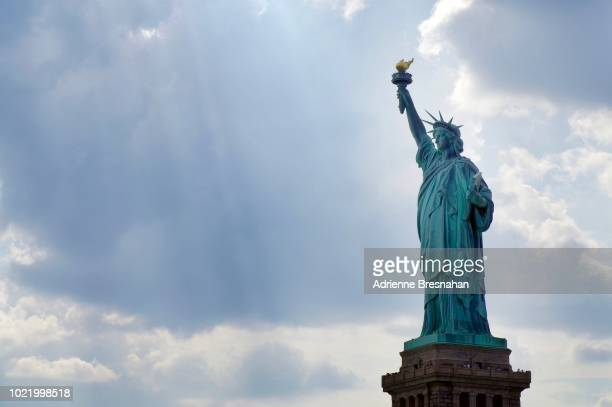 statue of liberty against clouds and blue sky - 自由の女神 ストックフォトと画像