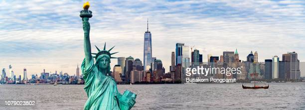 statue of liberty against one world trade center - statue of liberty stock pictures, royalty-free photos & images