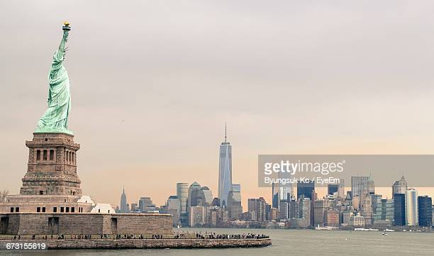 Statue Of Liberty And Cityscape Against Sky