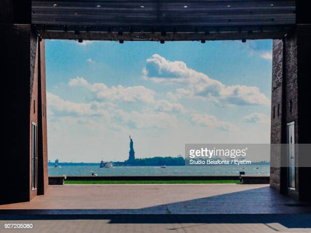 statue of liberty and hudson river against sky in city seen through entrance - studio city stock pictures, royalty-free photos & images