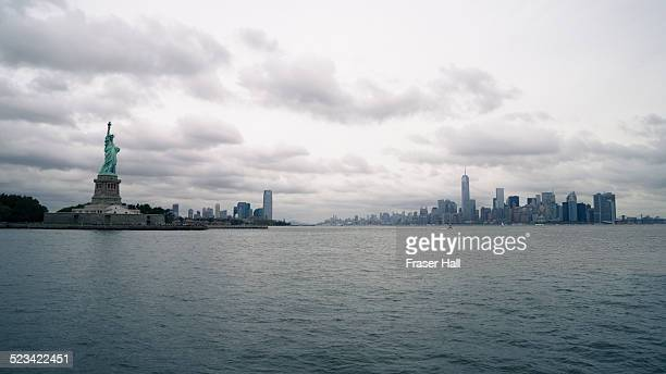 statue of liberty and manhattan sk - ニューヨーク湾 ストックフォトと画像