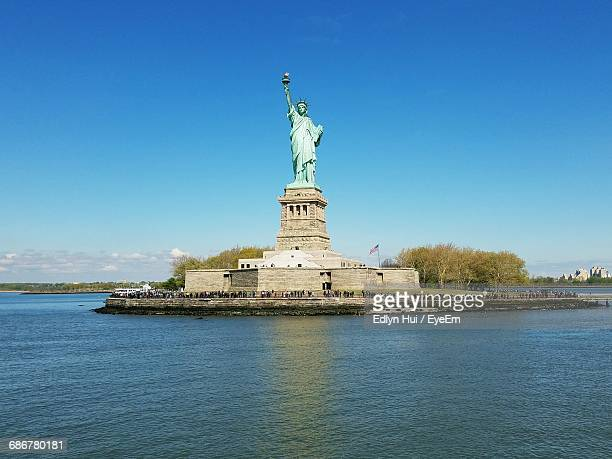Statue Of Liberty And Sea Against Clear Blue Sky On Sunny Day