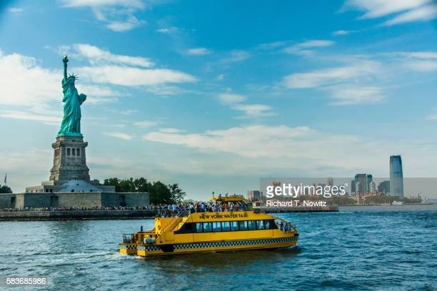 statue of liberty and tour boat and lower manhattan - schiffstaxi stock-fotos und bilder