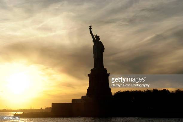 statue of liberty at sunset - carolyn ross stock pictures, royalty-free photos & images