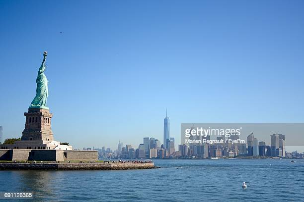 Statue Of Liberty By Cityscape Against Clear Sky