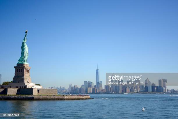Statue Of Liberty By Hudson River Against Clear Blue Sky In City