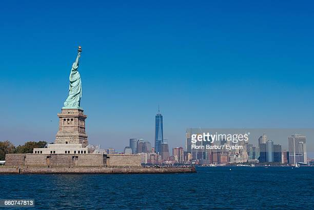 Statue Of Liberty By River Against Clear Sky