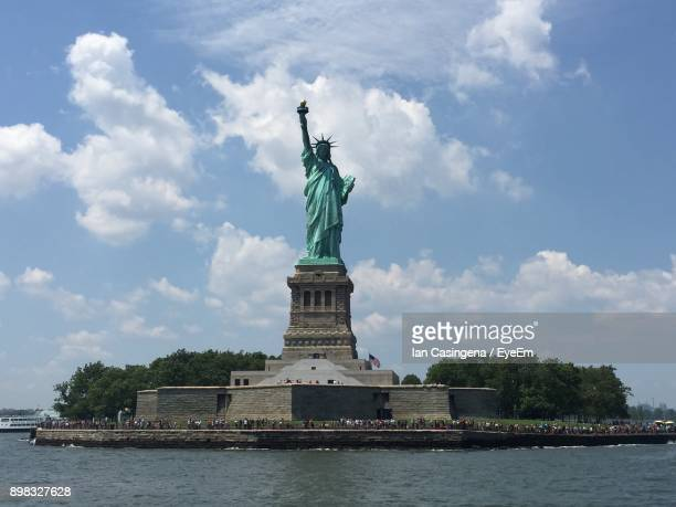 Statue Of Liberty By River Against Cloudy Sky