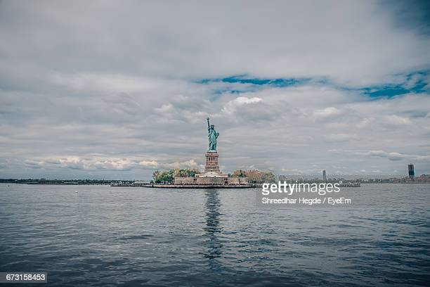 statue of liberty by sea against cloudy sky - monument stockfoto's en -beelden