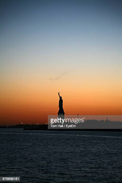 Statue Of Liberty By Sea Against Sky During Sunset