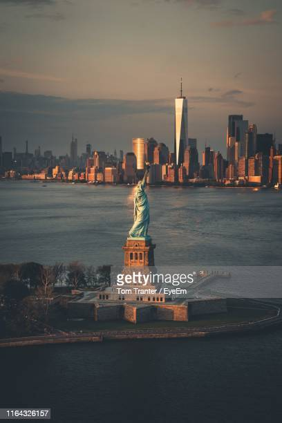 statue of liberty in city against sky - ニューヨーク湾 ストックフォトと画像