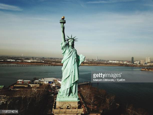 statue of liberty with city in background - statue of liberty stock pictures, royalty-free photos & images