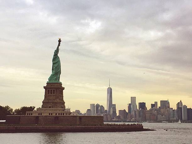Statue Of Liberty With Manhattan Skyline In Background Against Cloudy Sky Wall Art