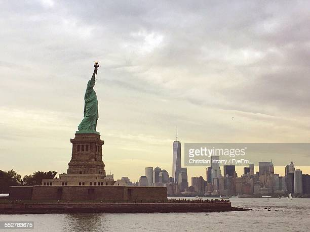 Statue Of Liberty With Manhattan Skyline In Background Against Cloudy Sky
