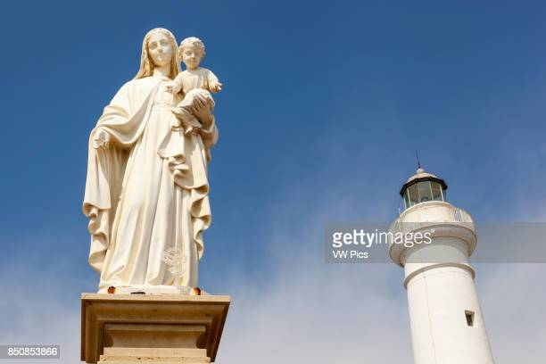 Statue of Mary holding Jesus and the lighthouse Punta Secca Santa Croce Camerina Sicily Italy