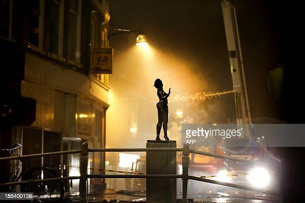 A statue of Mata Hari stands in front of burning buildings in the centre of Leeuwarden in Northern Netherlands on October 20 2013 The fire caused one...