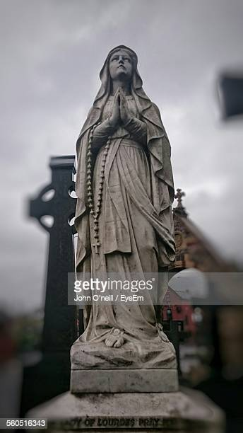 Statue Of Mother Mary With Hands Clasped In Cemetery