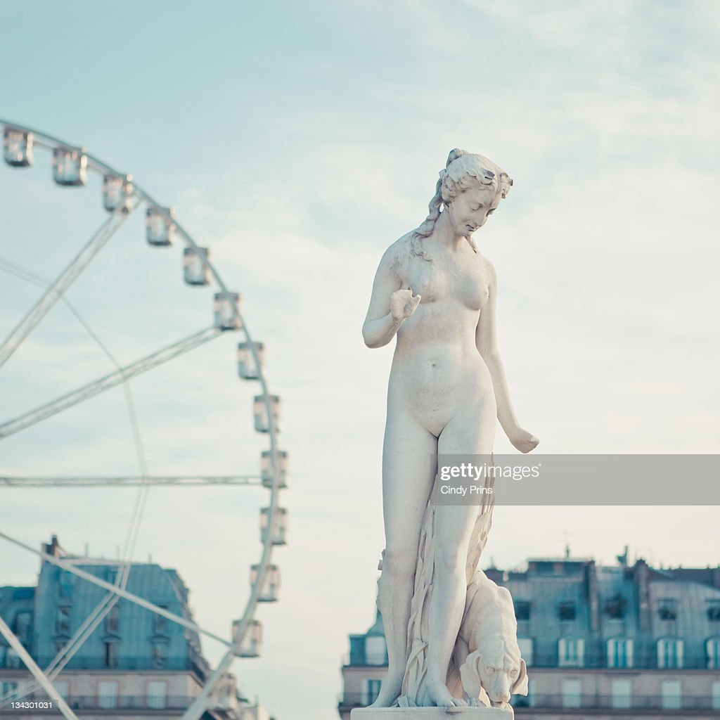 Statue of naked lady and carrousel in back : Stock Photo