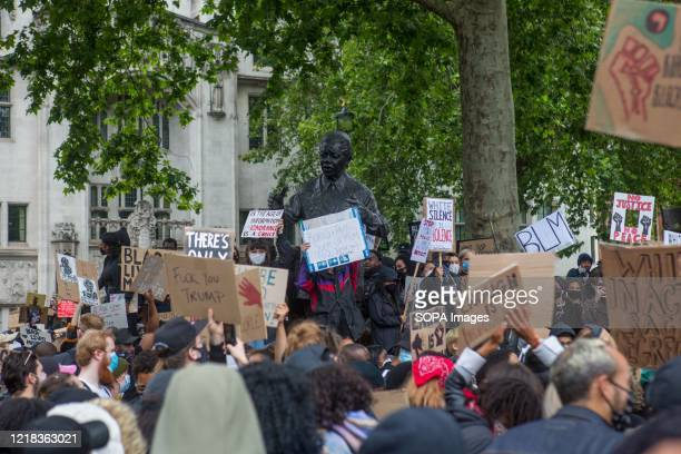 Statue of Nelson Mandela with protesters holding placards during the demonstration. Protesters from the Black Lives Matter campaign demand justice...