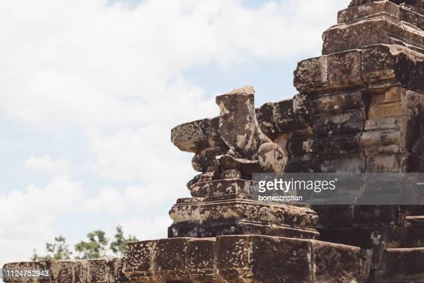 statue of old temple against sky - bortes stock-fotos und bilder