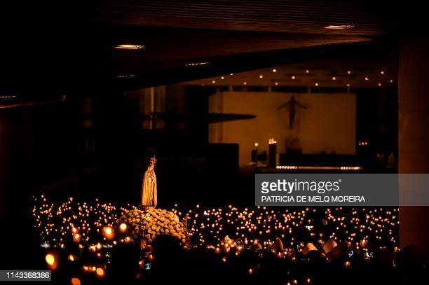 TOPSHOT A statue of Our Lady Fatima is carried during the candle procession at the Fatima shrine in Fatima central Portugal on May 12 2019 Thousands...