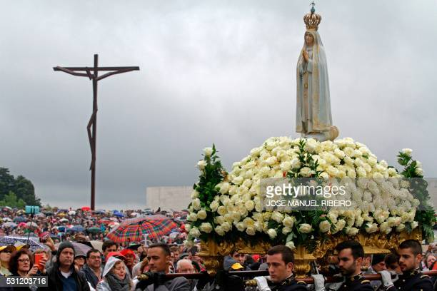 A statue of Our Lady of Fatima is carried to the Lord's table during a ceremony at the Fatima shrine in central Portugal on May 13 2016 Thousands of...