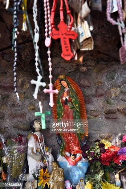 A statue of Our Lady of Guadalupe is among items left by worshippers in a shrine at El Santuario de Chimayo in the hispanic village of Chimayo New...
