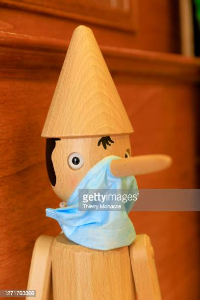 Statue of Pinocchio holds a protective mask in a Bartolucci shop on August 28 in Rome Italy. Pinocchio is the protagonist of the famous children's...