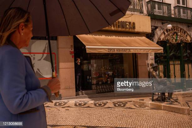 Statue of poet Fernando Pessoa stands close to a closed cafe on Rua Garret in the Chiado neighborhood of Lisbon, Portugal on Thursday, May 14, 2020....
