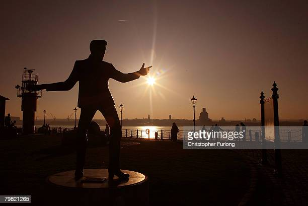 A statue of pop legend Billy Fury at Liverpool's Albert Dock sits against the backdrop of the setting sun on February 17 Liverpool England The...