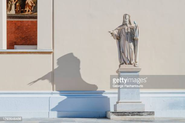 statue of priest with long shadow - greek orthodoxy stock pictures, royalty-free photos & images