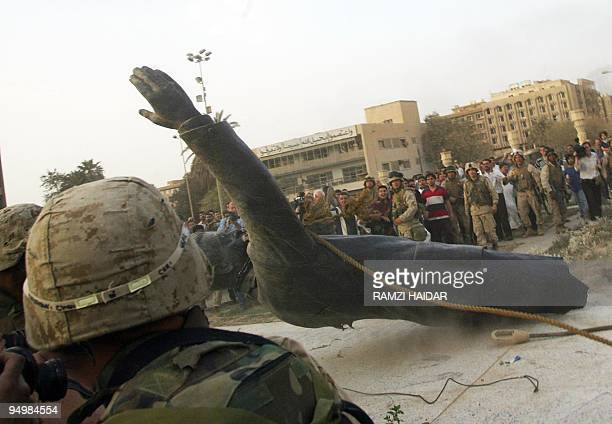 A statue of Saddam Hussein falls as it is pulled down by a US armored vehicle in Baghdad's alFardous square 09 April 2003 US troops moved into the...