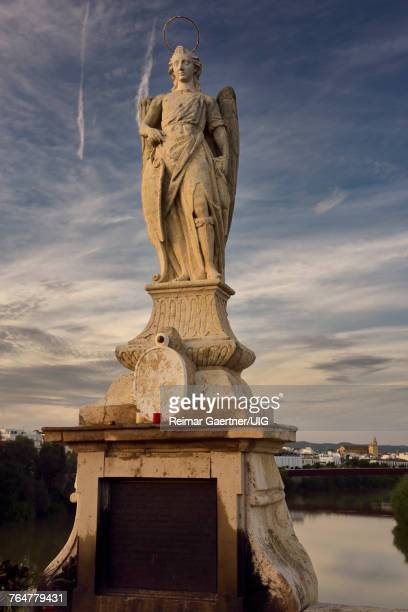 Statue of Saint Raphael at sundown on the Roman Bridge of Cordoba over the Guadalquivir River