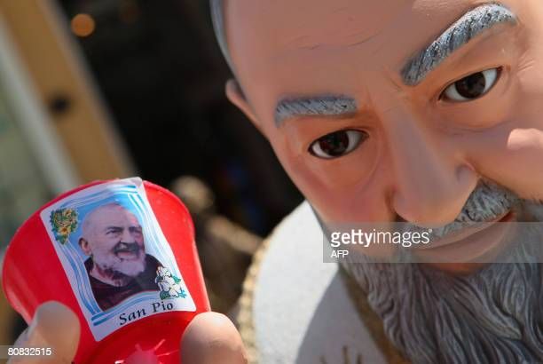 A statue of San Pio holds a votive candle Padre Pio in a religious gift store at San Giovanni Rotondo in the Puglia region in southern Italy on April...