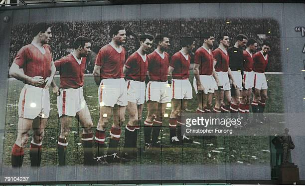 A statue of Sir Matt Busby stands in front of a giant mural commemorating the famous Busby Babes on the front of Manchester United's football stadium...