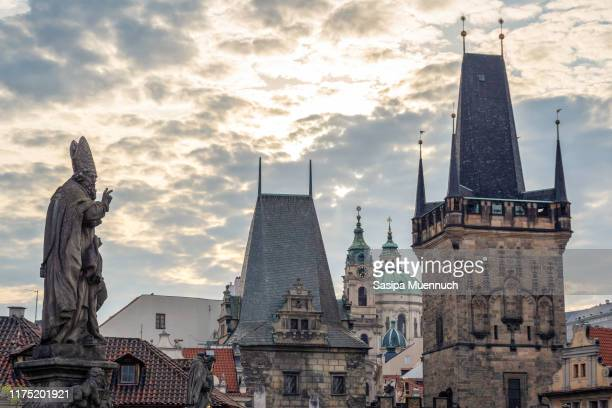 statue of st. adalbert on charles bridge and the lesser town bridge tower with dome of st. nicholas church on background - st nicholas' church stock pictures, royalty-free photos & images