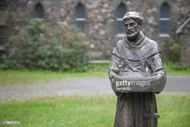 statue of st. francis of assisi in front of gothic church - st. francis of assisi stock photos and pictures