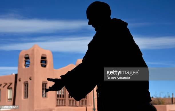 A statue of St Francis of Assisi is silhouetted in front of a landmark adobe building the Museum of Contemporary Native American Art in Santa Fe New...