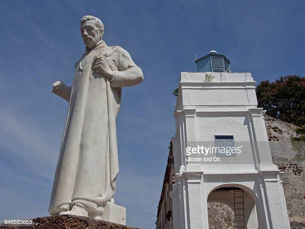 Statue of St Francis Xavier at St Paul's Hill with ruins of historical Portuguese fortress in Malacca a UNESCO World Heritage Site Malaysia
