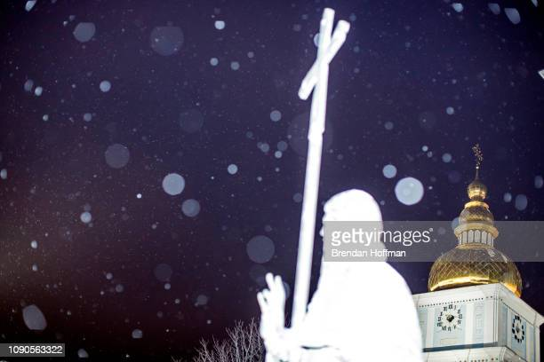 A statue of St Michael is illuminated by a camera flash in the snow at St Michael's GoldenDomed Monastery the main church of the new Orthodox Church...