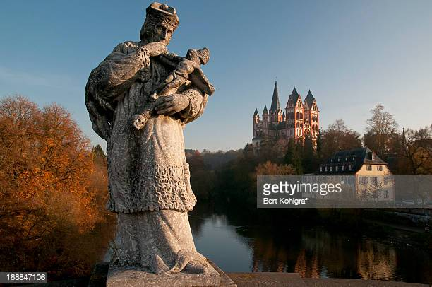 Statue of St. Nepomuk at the bridge over the Lahn river. In the background the Limburg Cathedral, Hessen, Germany