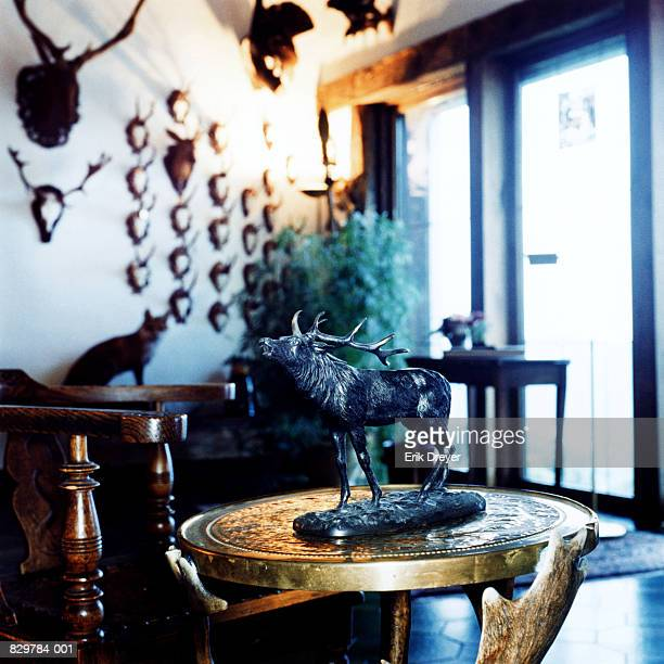 Statue of stag on table in room with animal head trophies