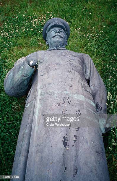 A statue of Stalin, relegated to the scrap heap after the fall of Communism, lying on the grass at the Lenin and Stalin Graveyard